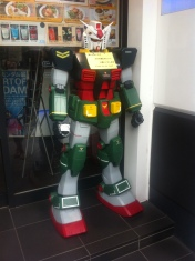 Gundam standing in front of the cafe telling you to wait patiently.